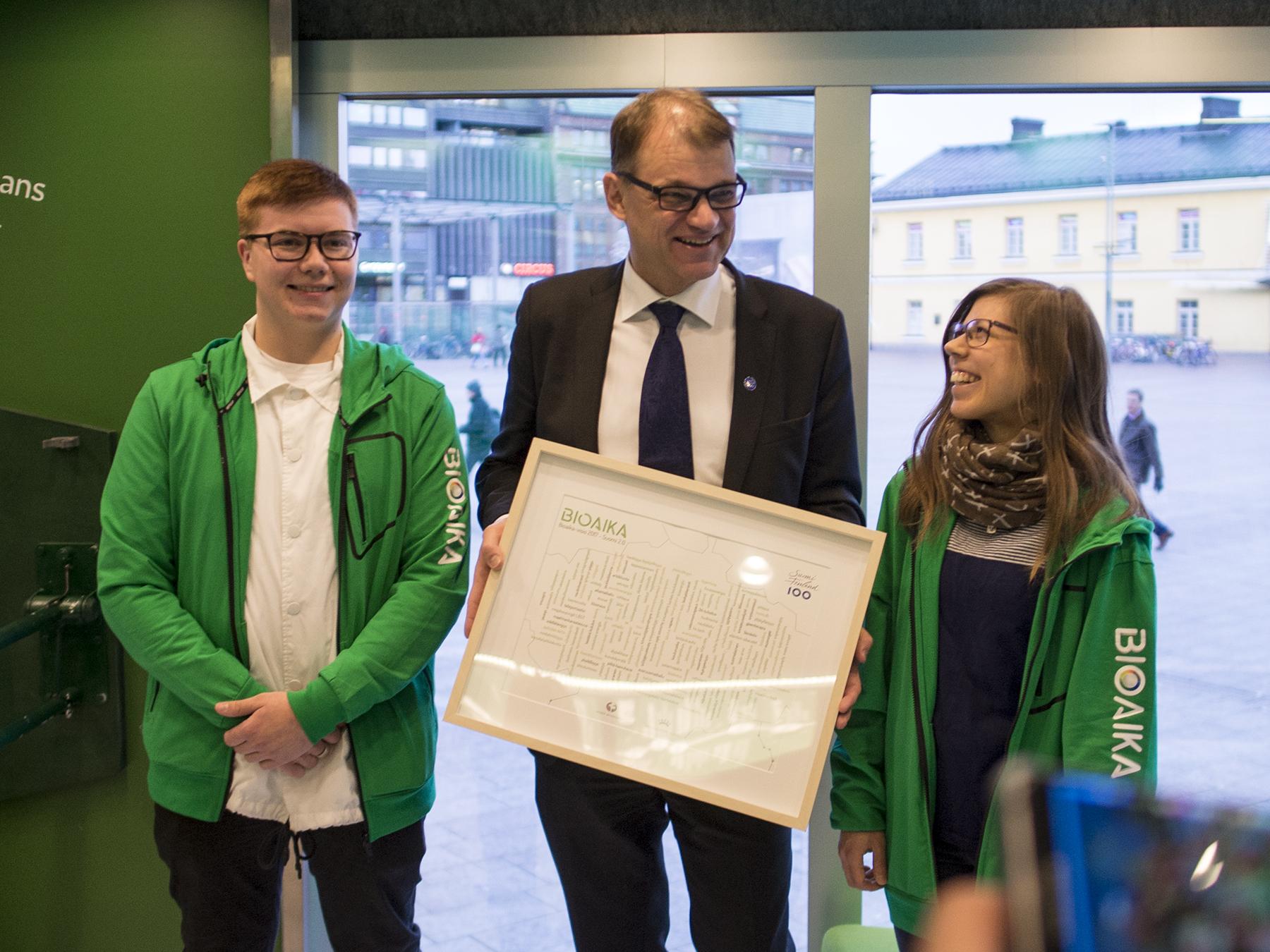 Students Oskari Mattinen and Maisa Hirvilammi hand over the Bio Era Vision to Finland's Prime Minister Juha Sipilä. Photo: Vilma Issakainen