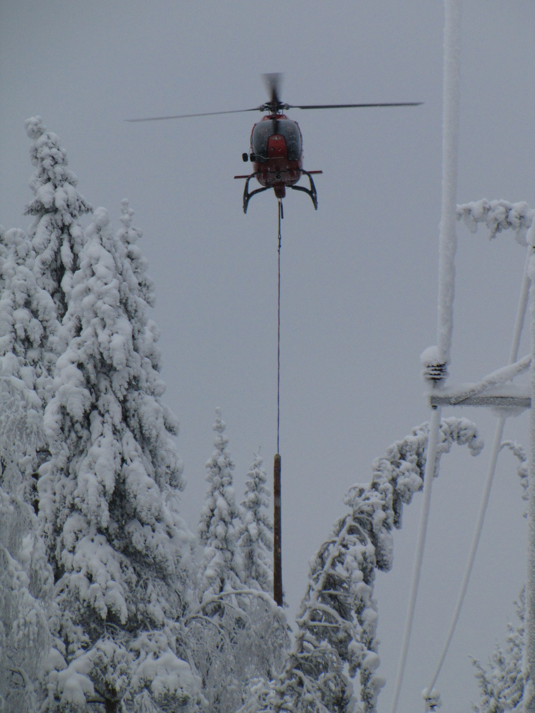 A helicopter is a great help in detecting, preventing and repairing the damage caused to power lines by snow load. It may take a long time to find a tree that has bent across or fallen down on a power line deep in the forest, unless you use a helicopter. They are also used to map areas with risk of snow load, and information on this can be sent to the maps of repair teams via the mobile network. The photo shows snow being dropped with the help of a helicopter pulling a short log attached to a wire rope along the edge of the power line corridor. The log hits the trees bent across the corridor and causes the snow to fall off. For the pilot, this is an extremely demanding task, as the log must be prevented from touching the power lines at all times. Photo: Elenia