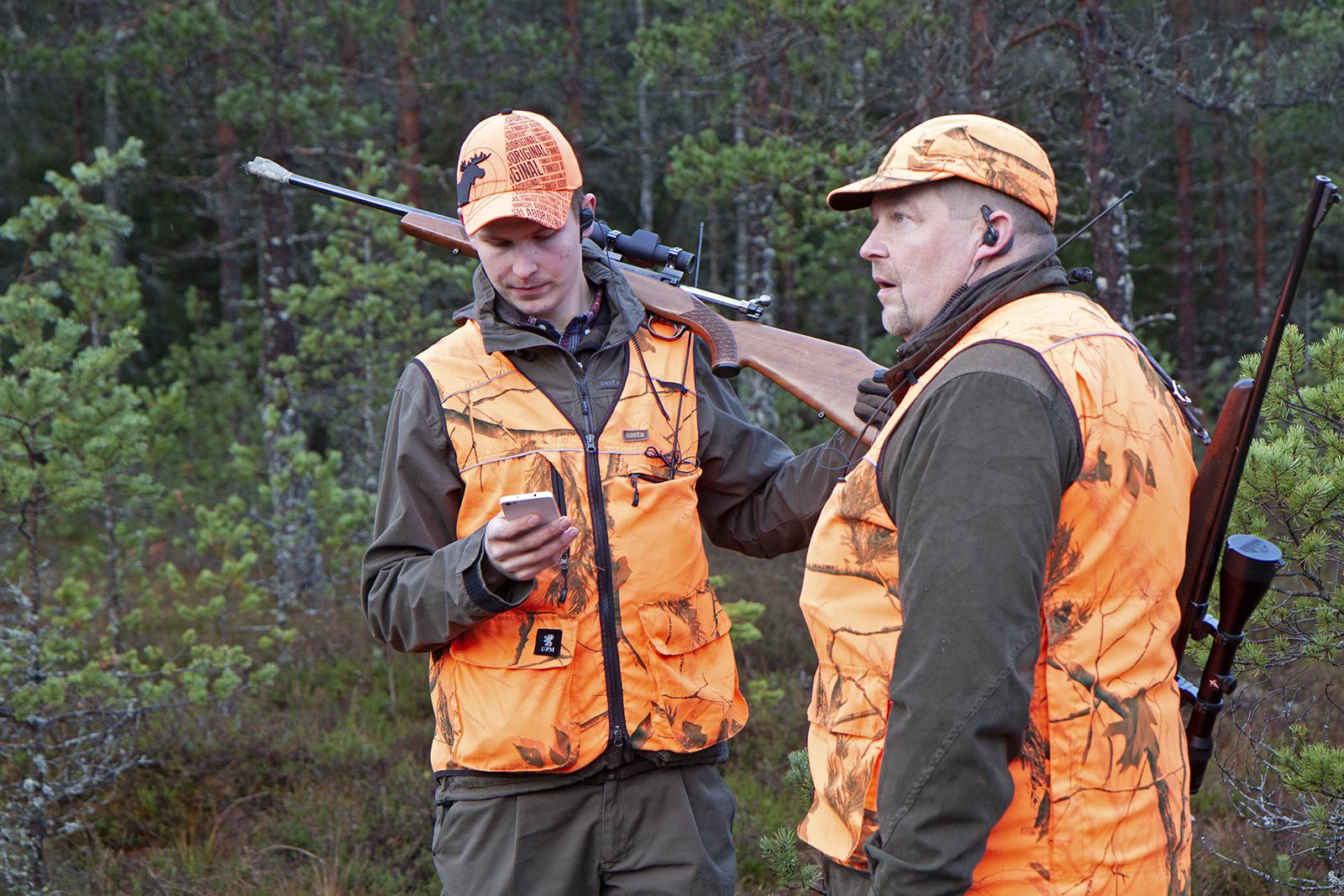 Perttu Valosen ja Juha-Matti Valosen tärkein varuste metsään lähtiessä on kiikari. Oranssit vaatteet ovat turvallisuuden vuoksi metsästyksessä pakolliset. Kuva: Anna Kauppi