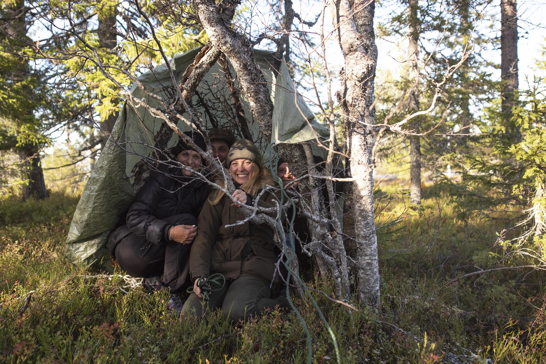 Metsähallituksen työpajassa koeteltiin osallistujien selviytymistaitoja. Metsässä piti muun muassa rakentaa suoja pressusta narun avulla. Nuoret alkavat kiinnostua selviytymistaidoistaan metsässä 14–16 vuoden isässä. Kuva: Vilma Issakainen