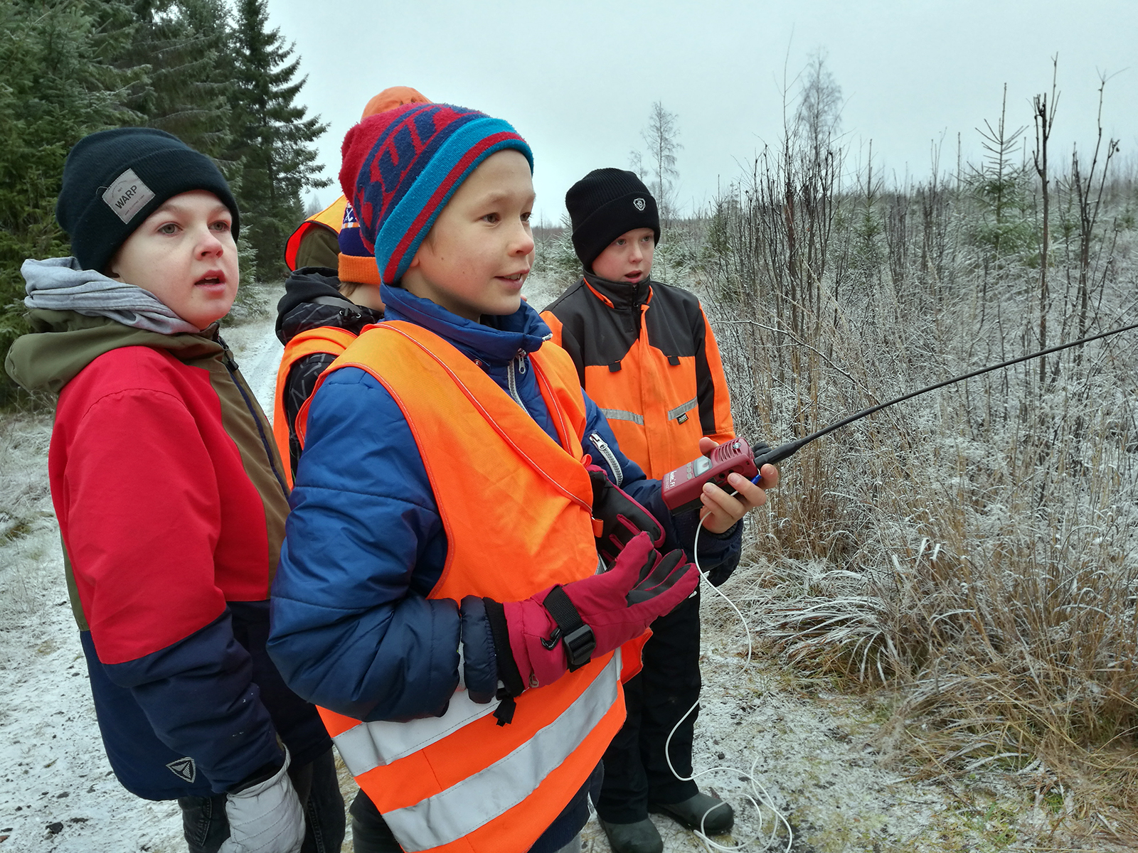 Orange clothing and a walkie-talkie are basic equipment for hunters, Tuomas, Oskari and Samu know. Photo: Anna Kauppi