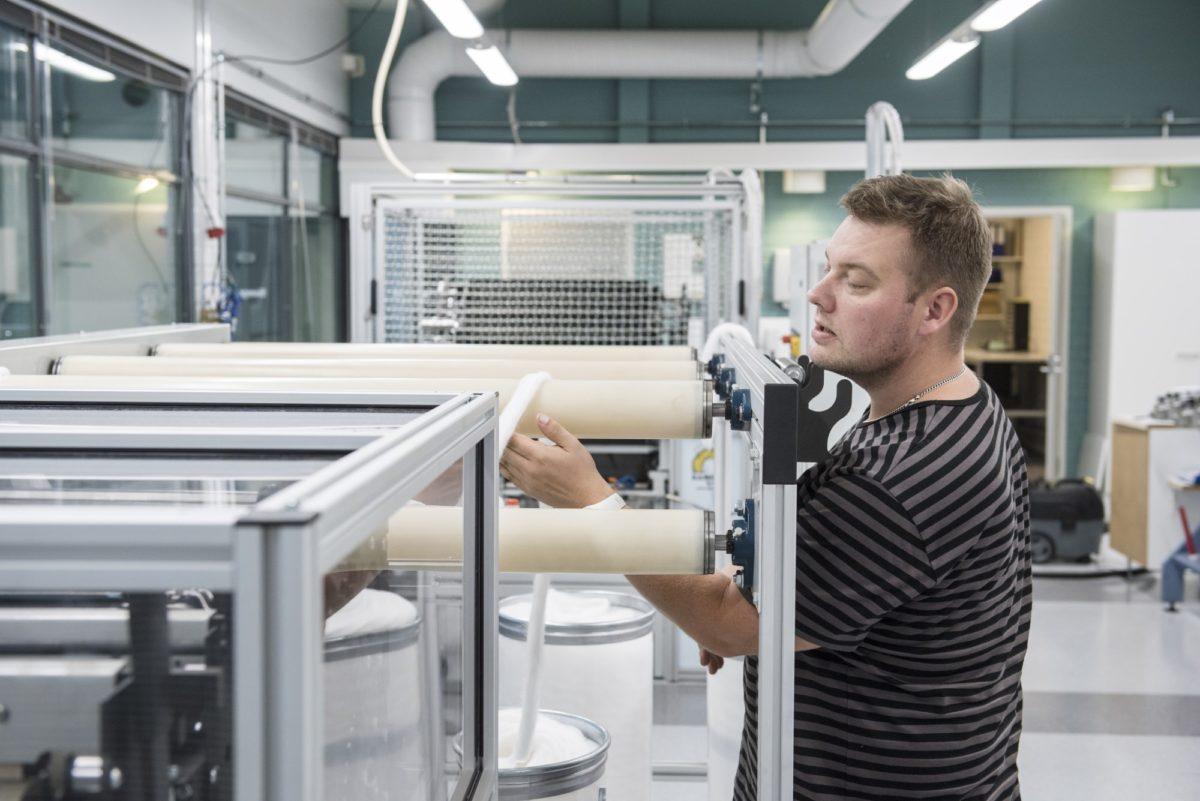 Arto Salminen käsittelee valmista kuitua karstaus- ja kehräyslinjalla. Spinnovan kuidusta kehrätään lankaa ja langasta valmistetaan kankaita. Kuva: Spinnova