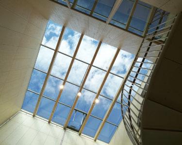 Puukoulu saa valoa suurten kattoikkunoiden kautta
