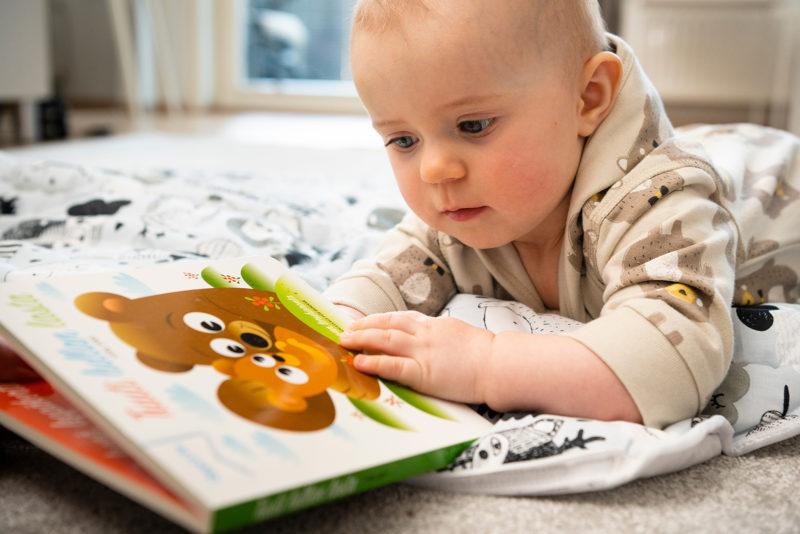 Vauva tutkii äitiyspakkauksen ensikirjaa. Kuva: Kela, Veikko Somerpuro