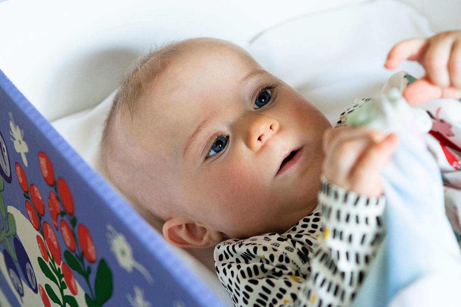 Vauva pötköttää äitiyspakkauslaatikossa. Kuva: Kela, Veikko Somerpuro